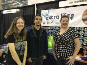 Two women and one man posing in front of an Extra Life banner during a Wizard World event.