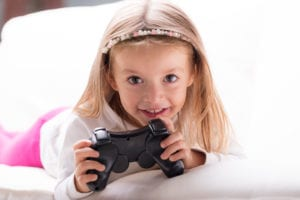 Adorable playful pretty little blond girl with a TV game controller lying on her bed grinning happily at the camera
