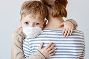Little boy in medical mask hugging crop mother and looking at camera during coronavirus outbreak